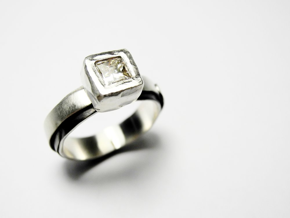 Princess cut diamond in carved rub over setting