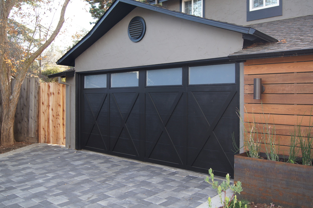 Instead of replacing the nearly new garage door, we removed the faux hardware and window pane dividers, painted it black to match the trim (and hide the wood grain embossing in the metal) and used a film on the windows to match the new glass panel front door.