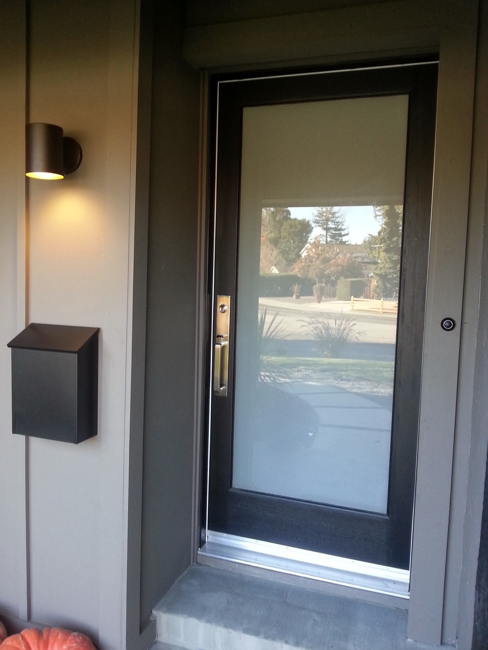 New laminated glass panel front door with lovely hardware, new lighting, mailbox and board and baton siding to cover the old brick, which also allowed us to run electrical for a hardwired doorbell.