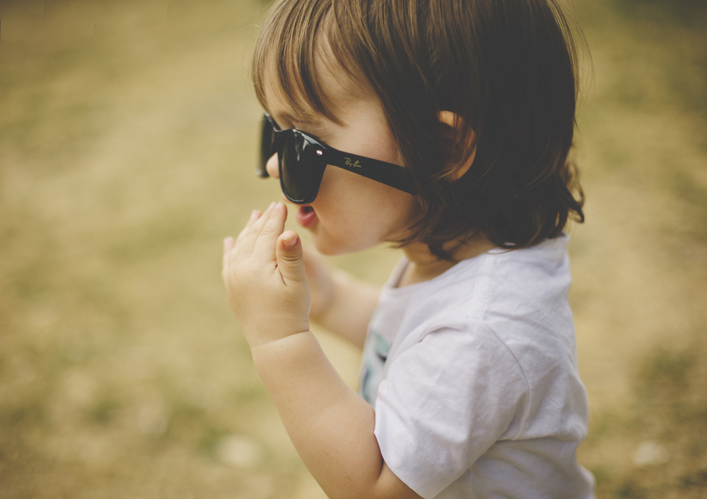 Toddler trying on Mum's sunglasses!
