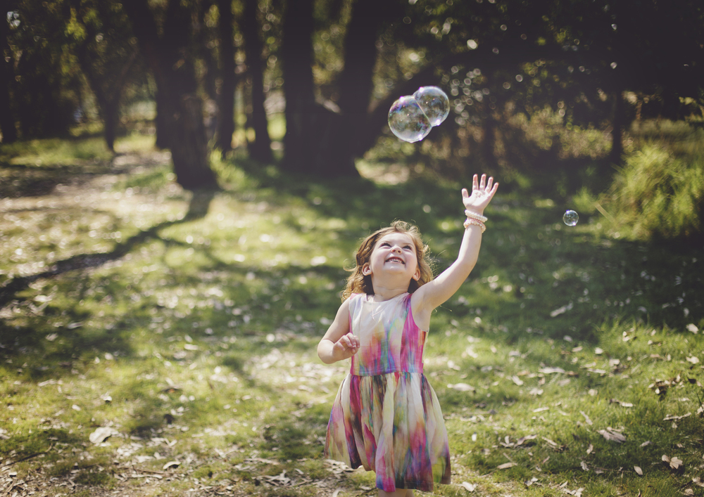 Little girl catching bubbles!