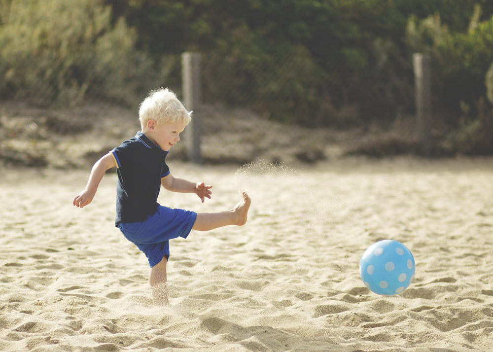 Toddler kicking the ball at the beach!