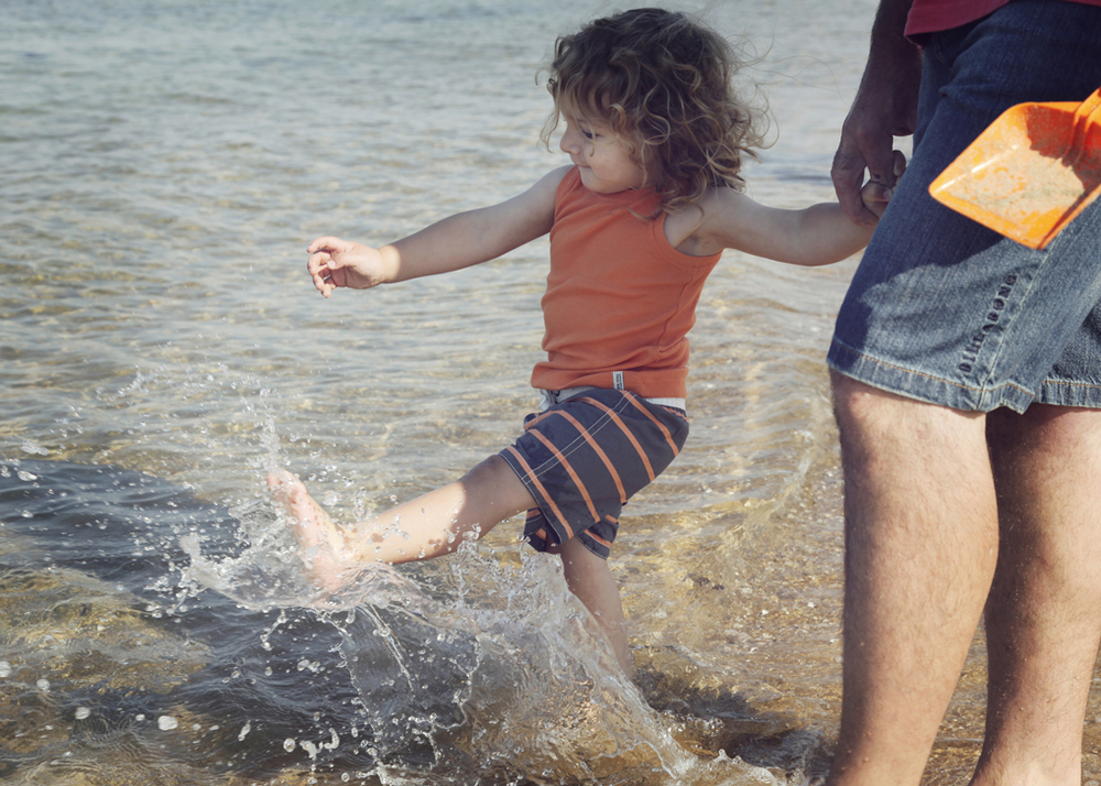 Little boy kicking the water at the beach!