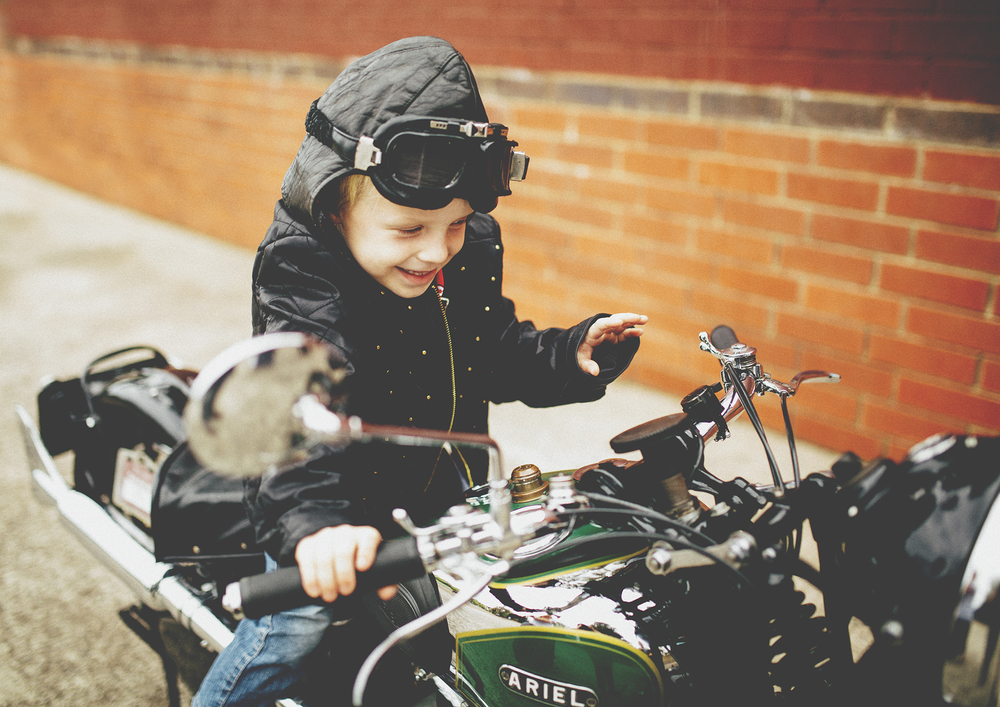 A little boy pressing the horn on the motorbike!