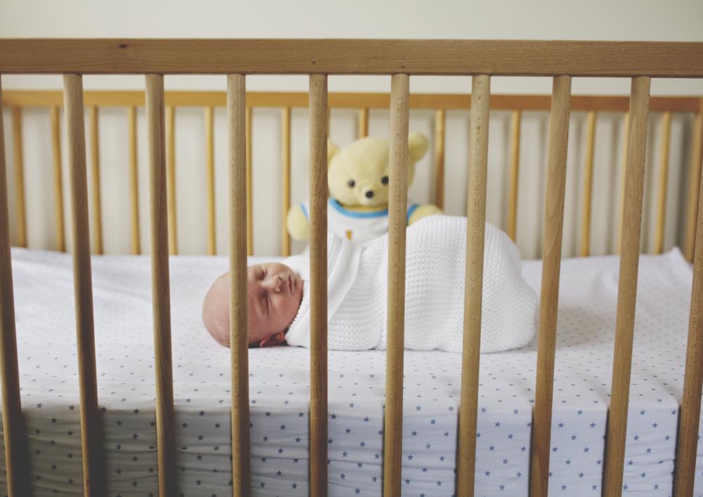 Side shot of newborn in cot - Newborn Photography Melbourne