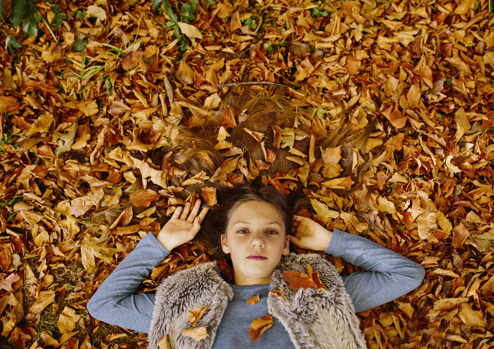Autumn leaves covering little girl's hair!