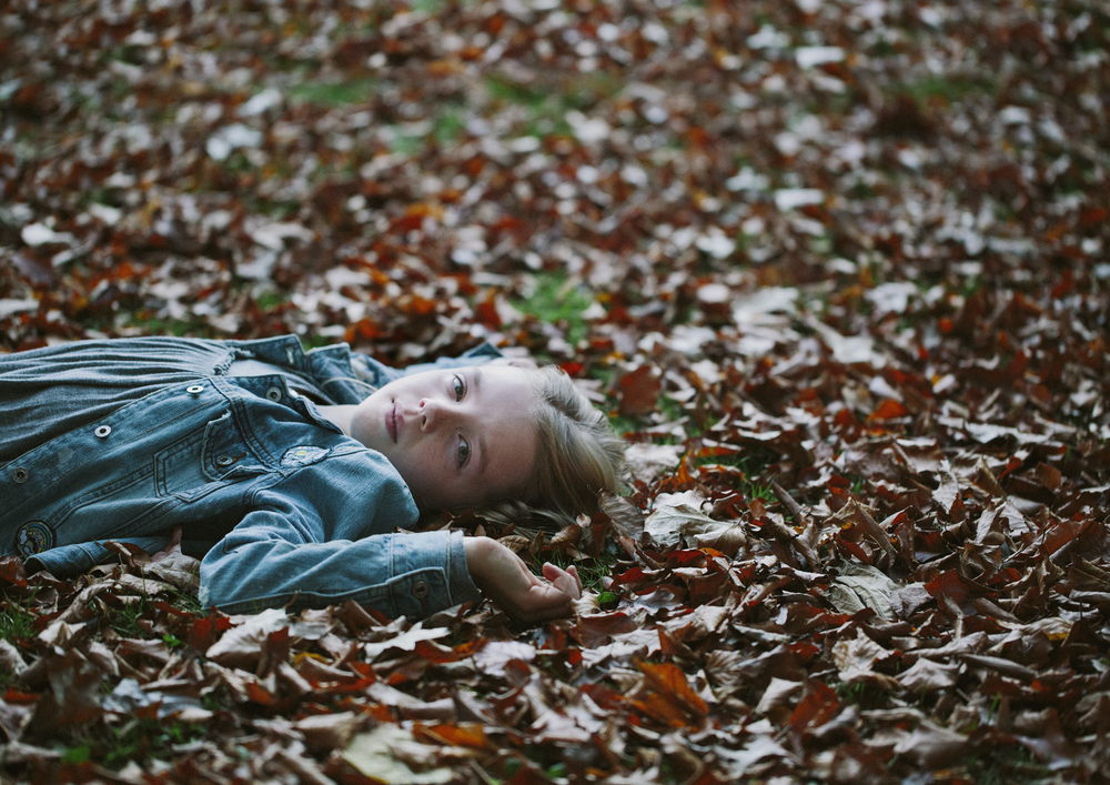 Child lying in the Autumn leaves!
