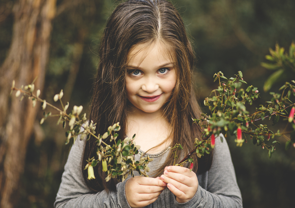 Little girl holding flowering shrubs from the native reserve!