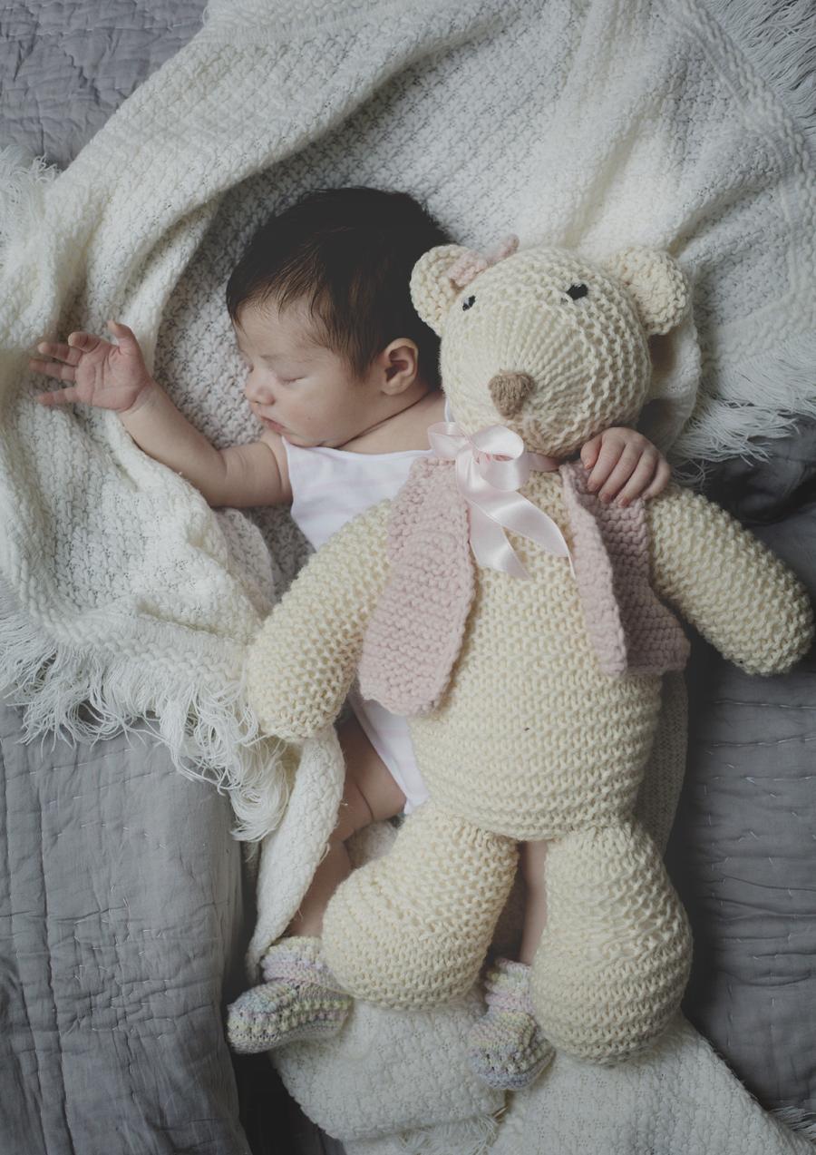 Tiny newborn baby girl with big teddybear