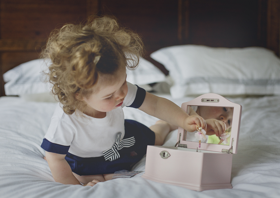 Photography of toddler playing with her jewellery box