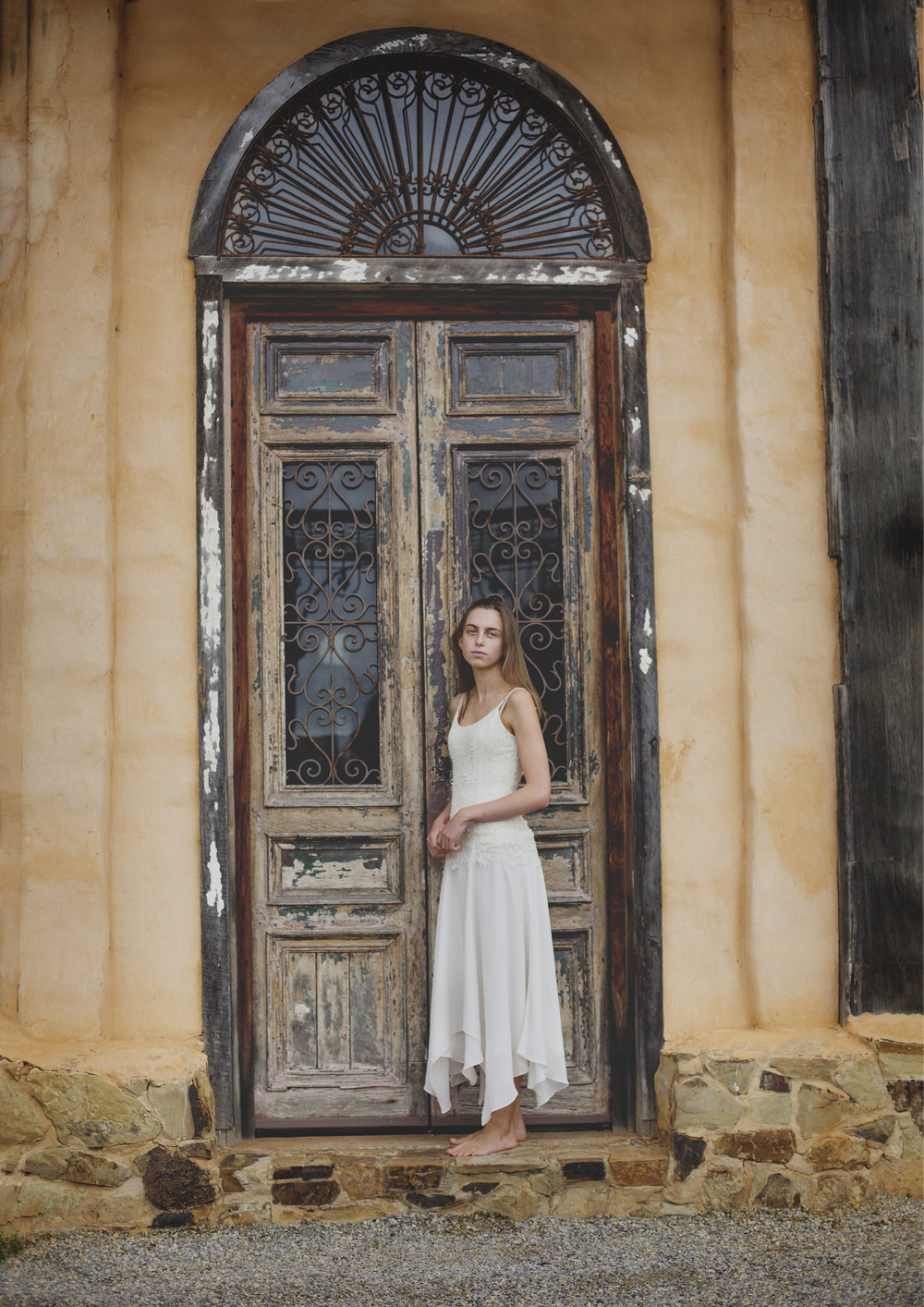 Teenage girl photographed outside against vintage door
