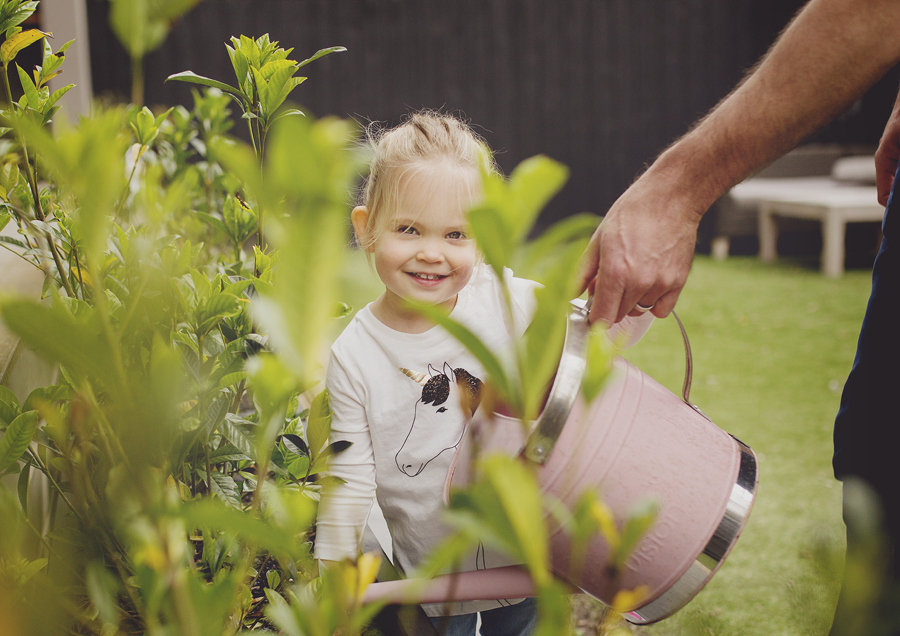 Toddler watering the garden with her Dad!