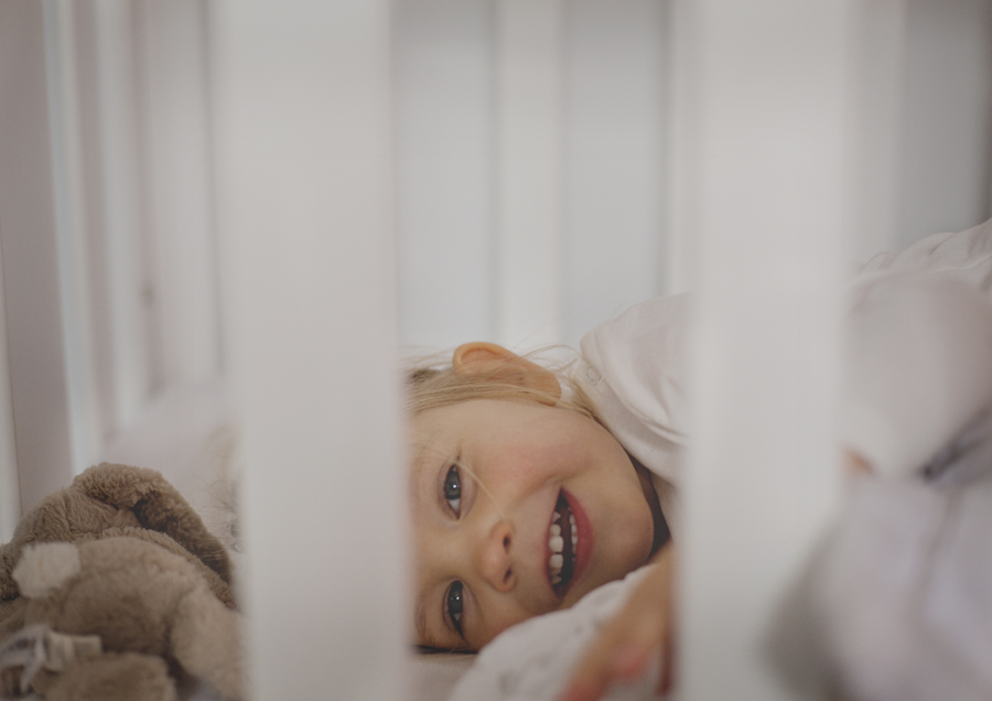 Toddler pretending to go to sleep in her cot