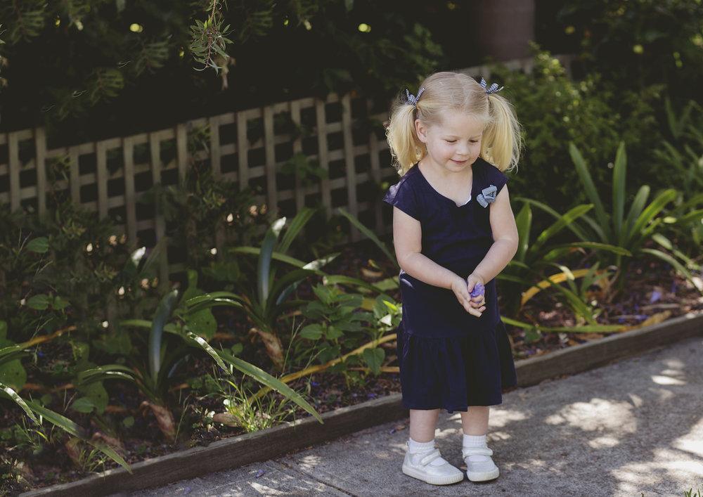 Toddler about to throw Jacaranda petals