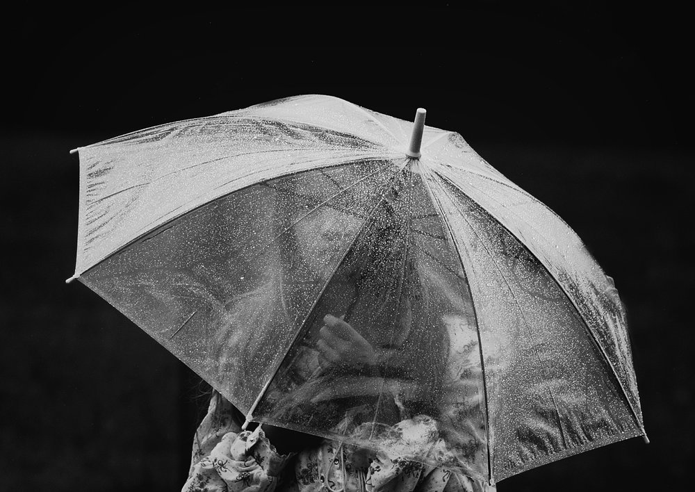 Black and White image of young girl out in the rain