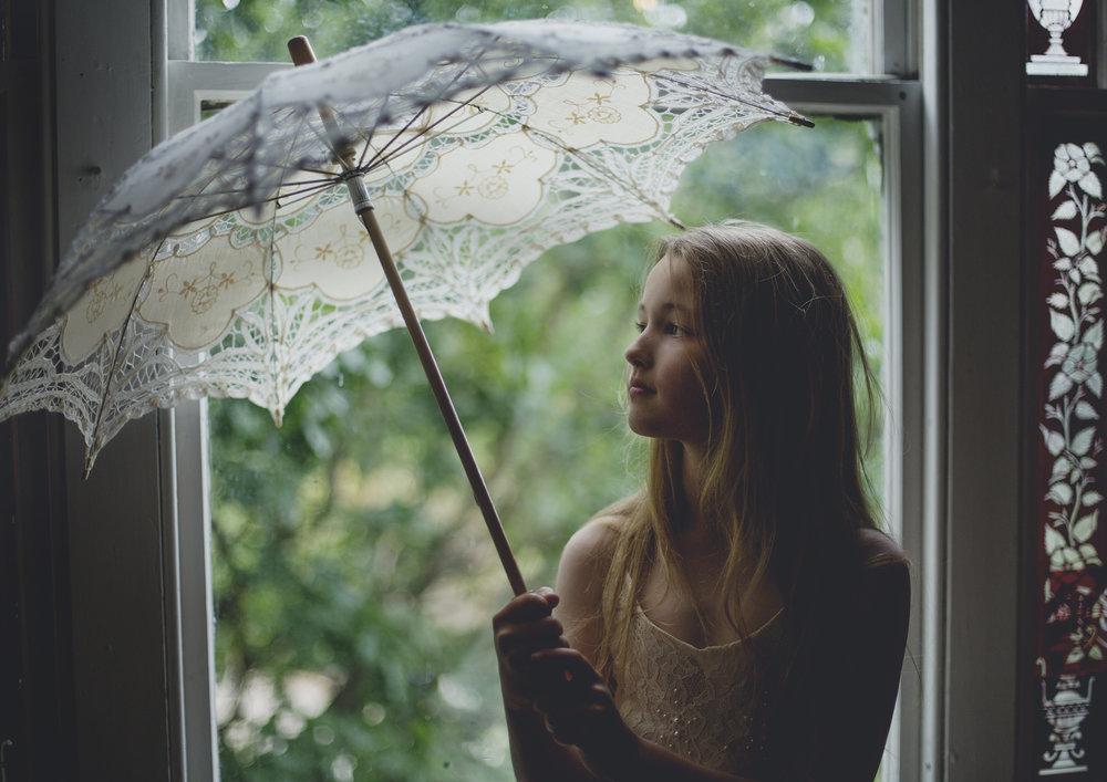 Child photographed holding vintage umbrella