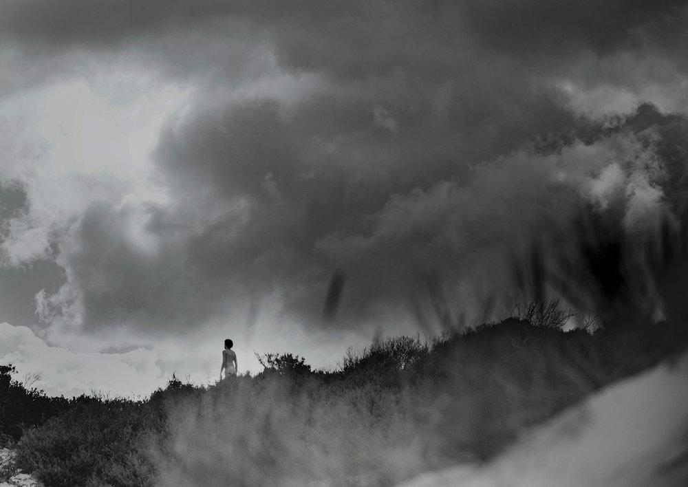 Teenage boy climbing the cliffs at the beach