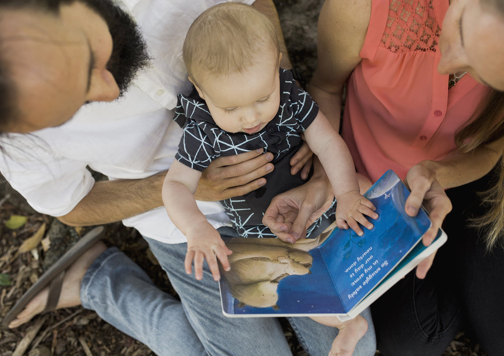 New parents reading to their 6 month old baby boy