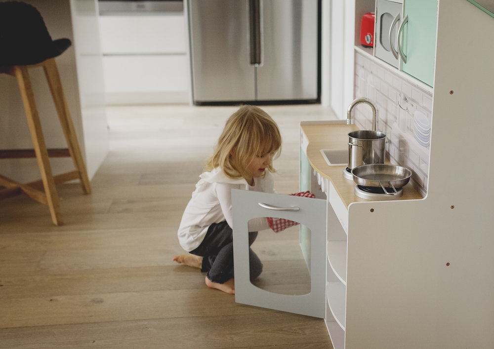 Little girl playing with her toy kitchen