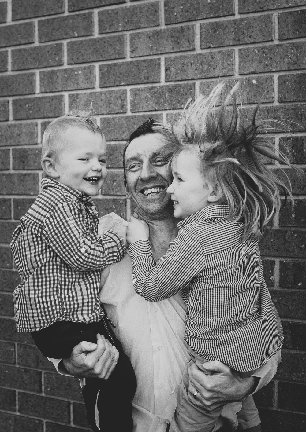 Dad jumping holding both his boys!