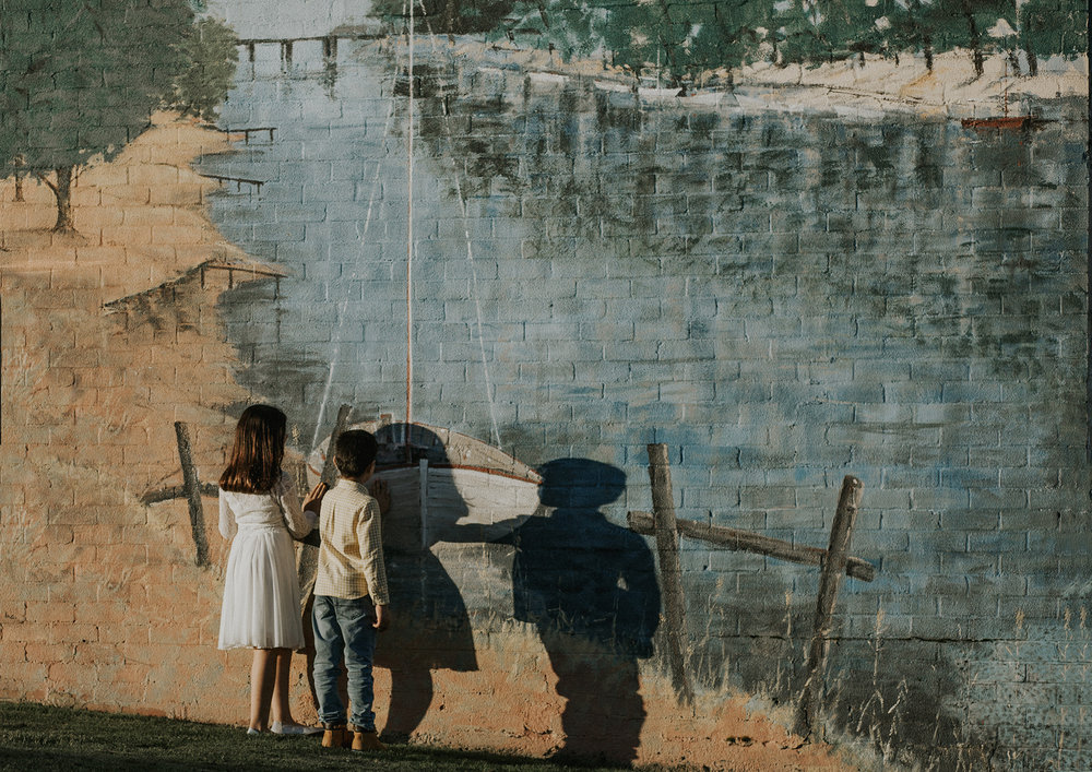 Children admiring a mural on side of brick wall