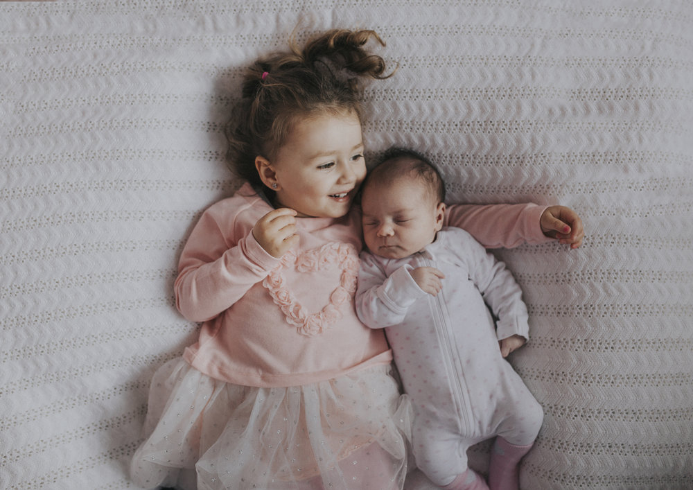 Toddler holding her newborn baby sister