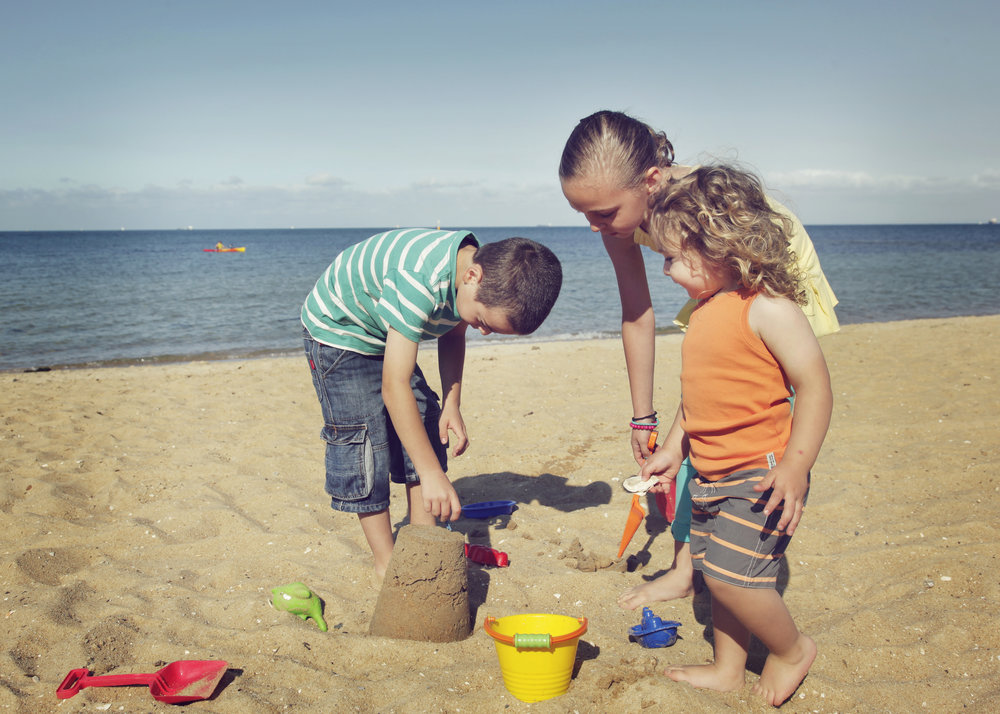 Children having fun in the sand at the beach!