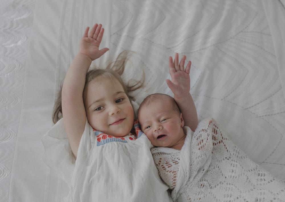 Toddler cradling her newborn baby sister