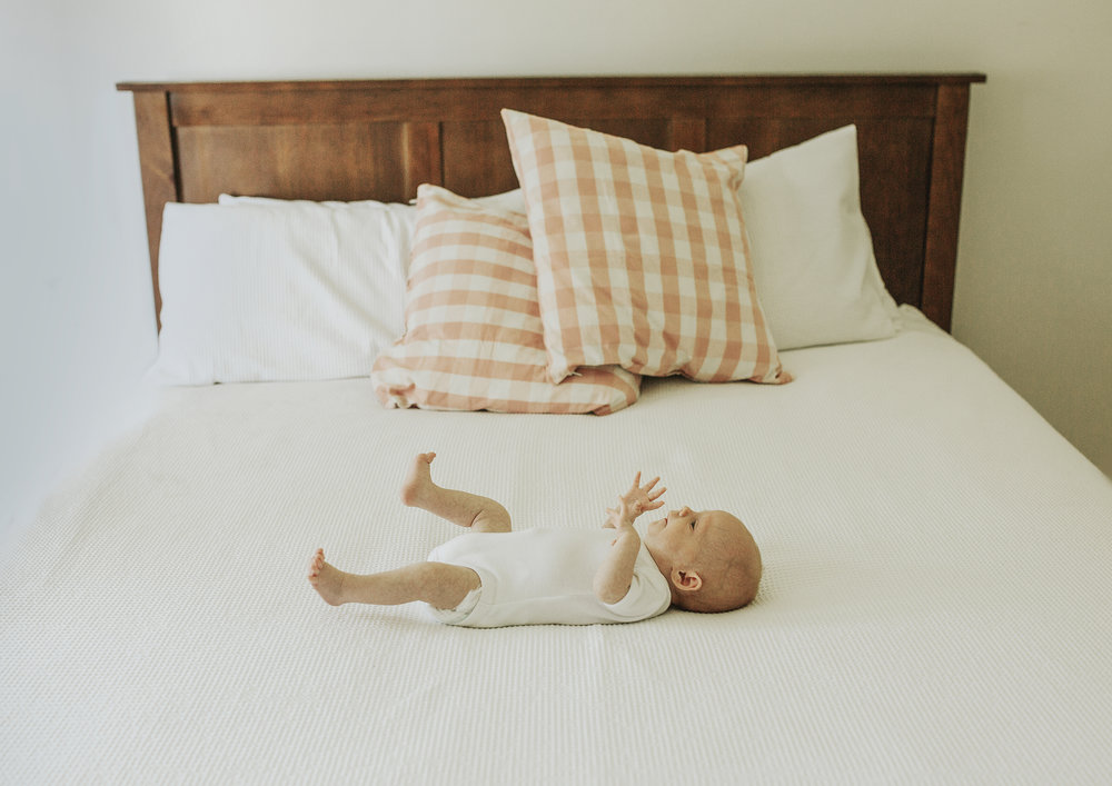 Tiny newborn baby on her parent's large bed