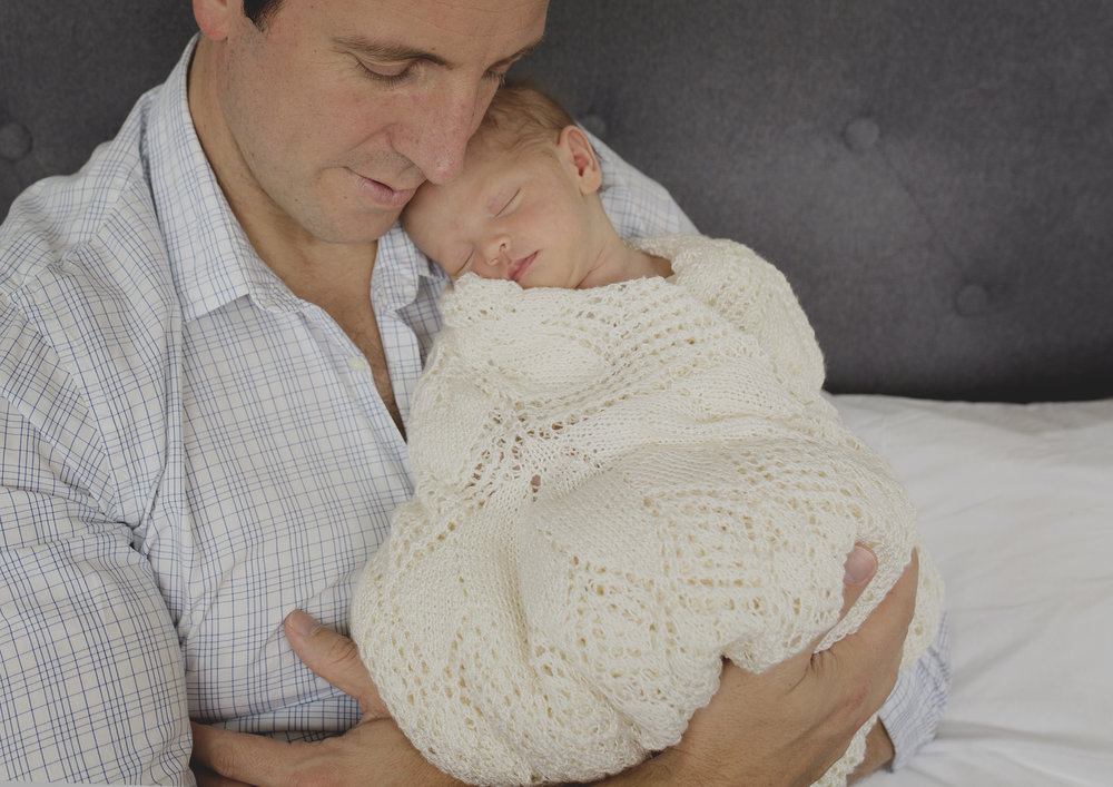 Newborn baby girl nestling into her father