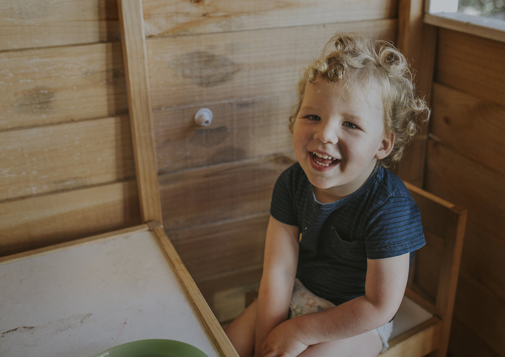 Toddler playing inside his cubby