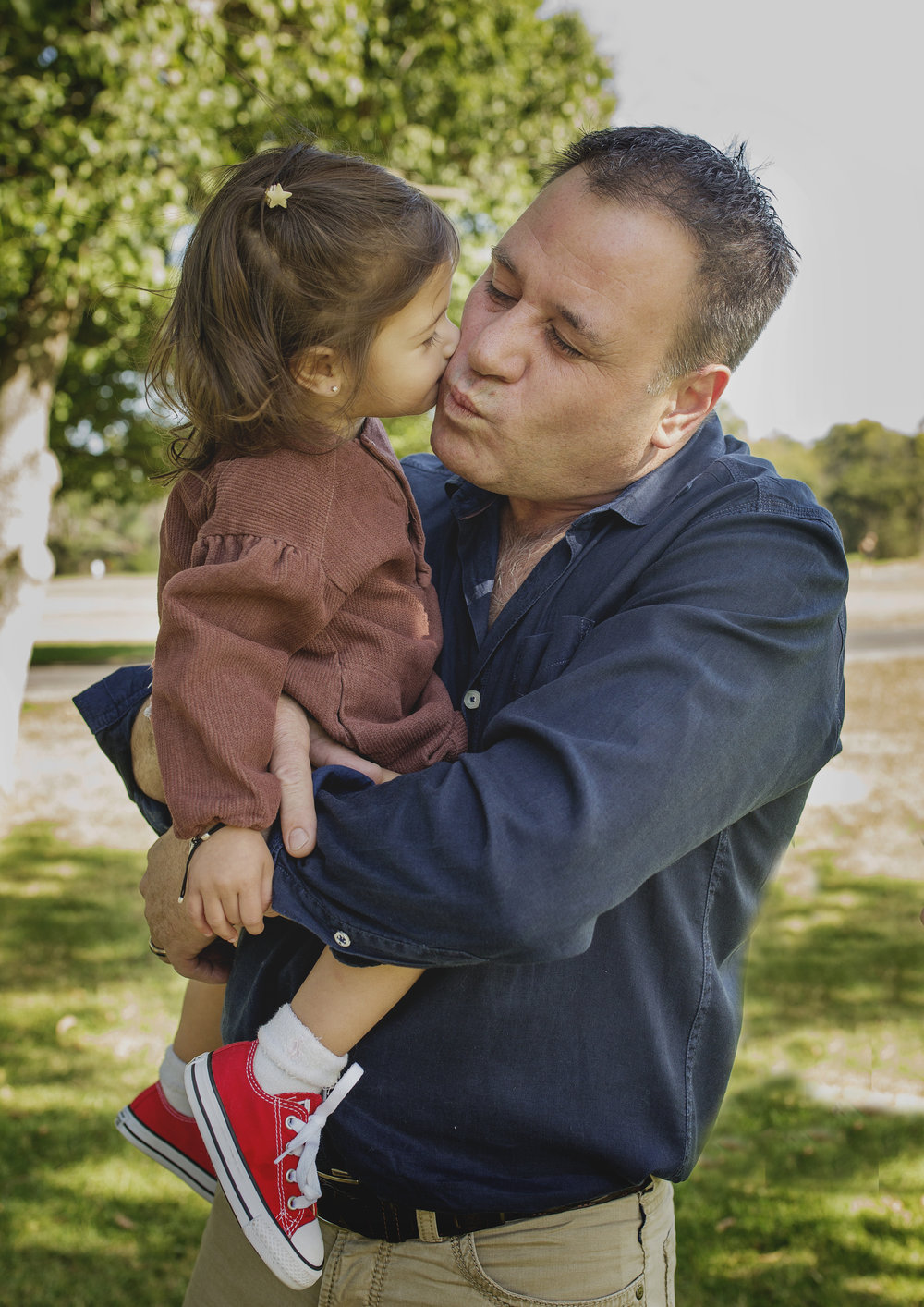Little girl kissing her daddy!