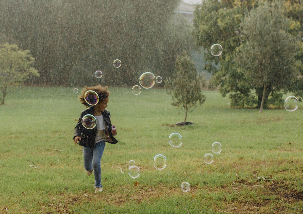 Child chasing bubbles in the rain
