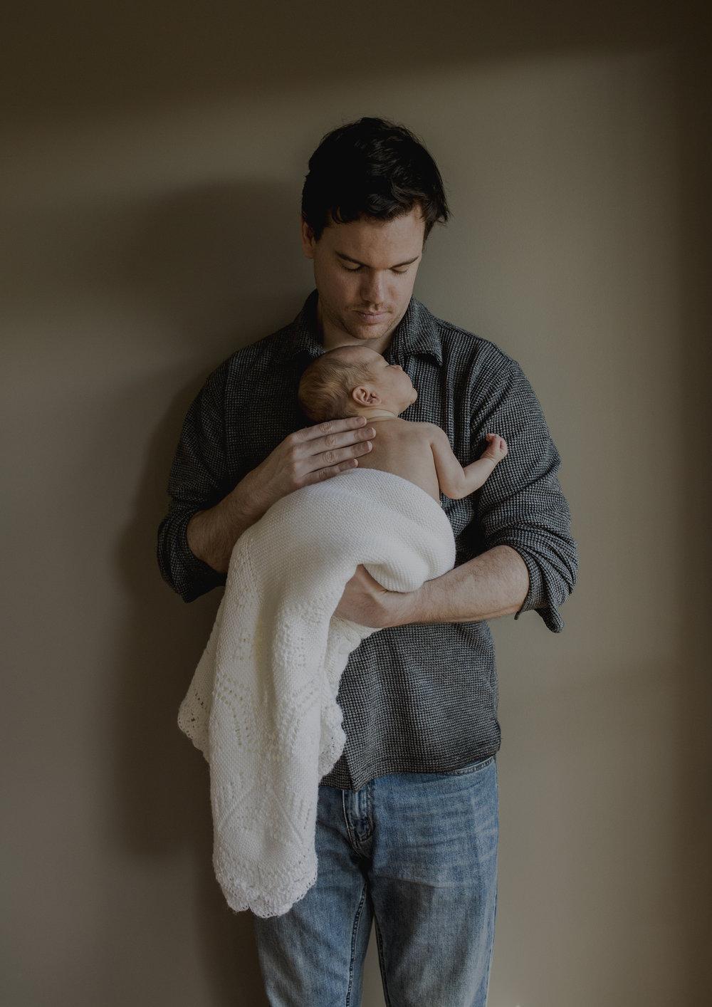 New Dad cuddling his newborn baby girl to sleep