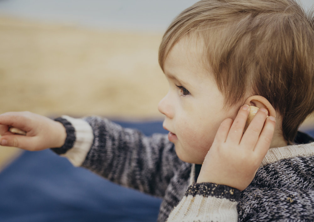 Toddler trying to hear the sea in a seashell