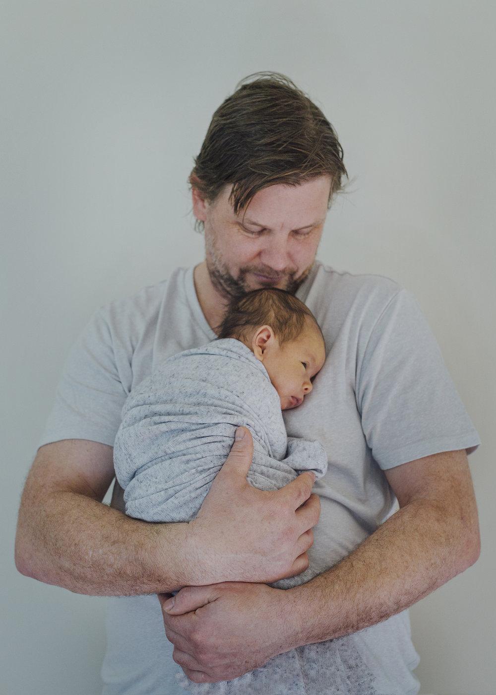New Dad cuddling his newborn baby son