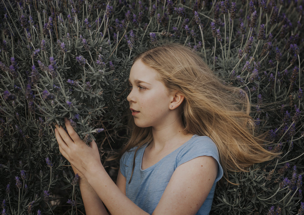 Tween girl smelling the lavender bush