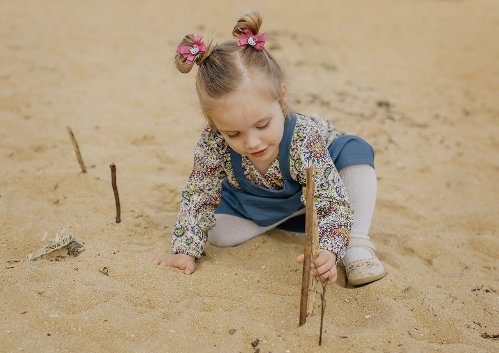 Toddler playing with sticks in the sand