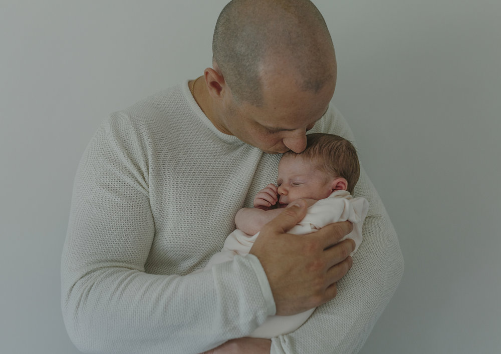 New Dad cuddling his newborn baby girl