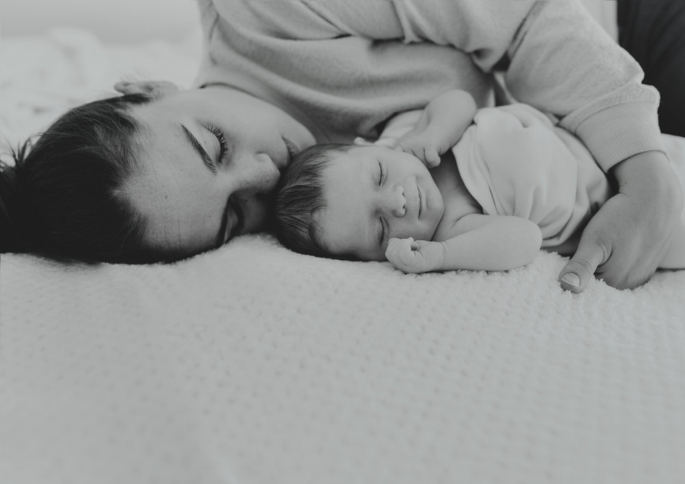 New mother cuddling her newborn baby daughter