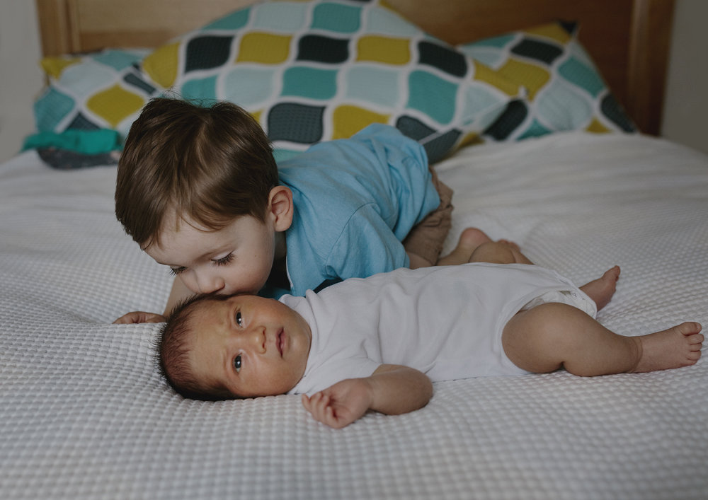 Big brother kissing his newborn baby brother