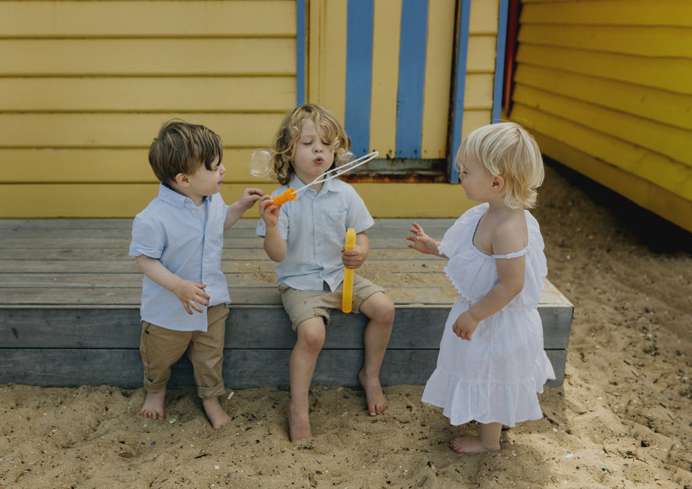 Children blowing bubbles down at the beach