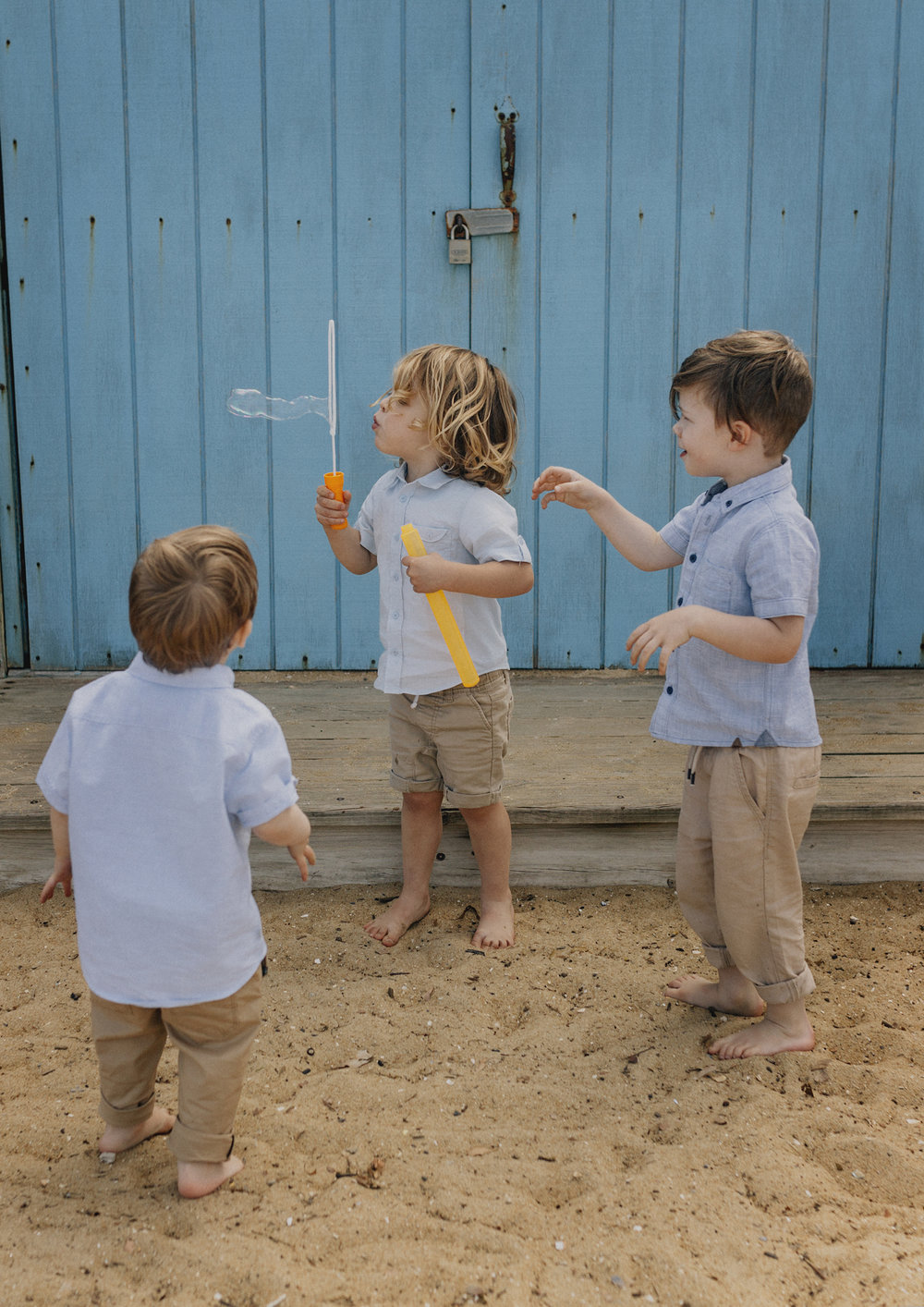 Cousins having fun blowing bubbles at the beach