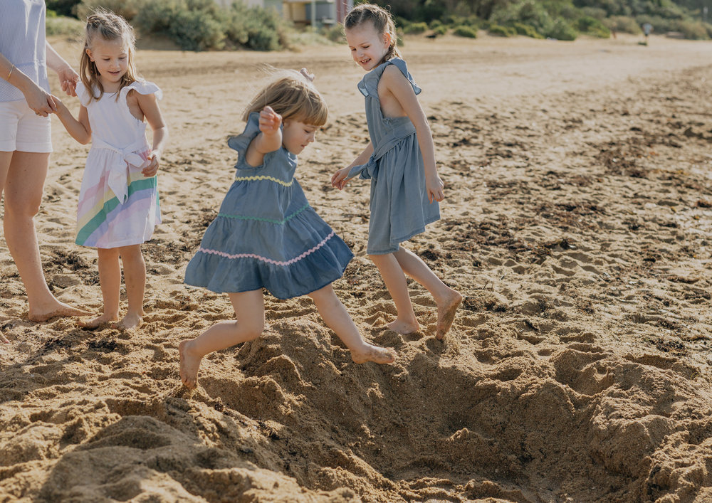 Children jumping in a hole down at the beach