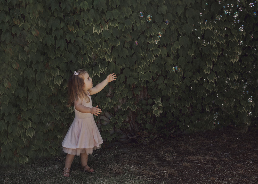 3 year old toddler chasing bubbles