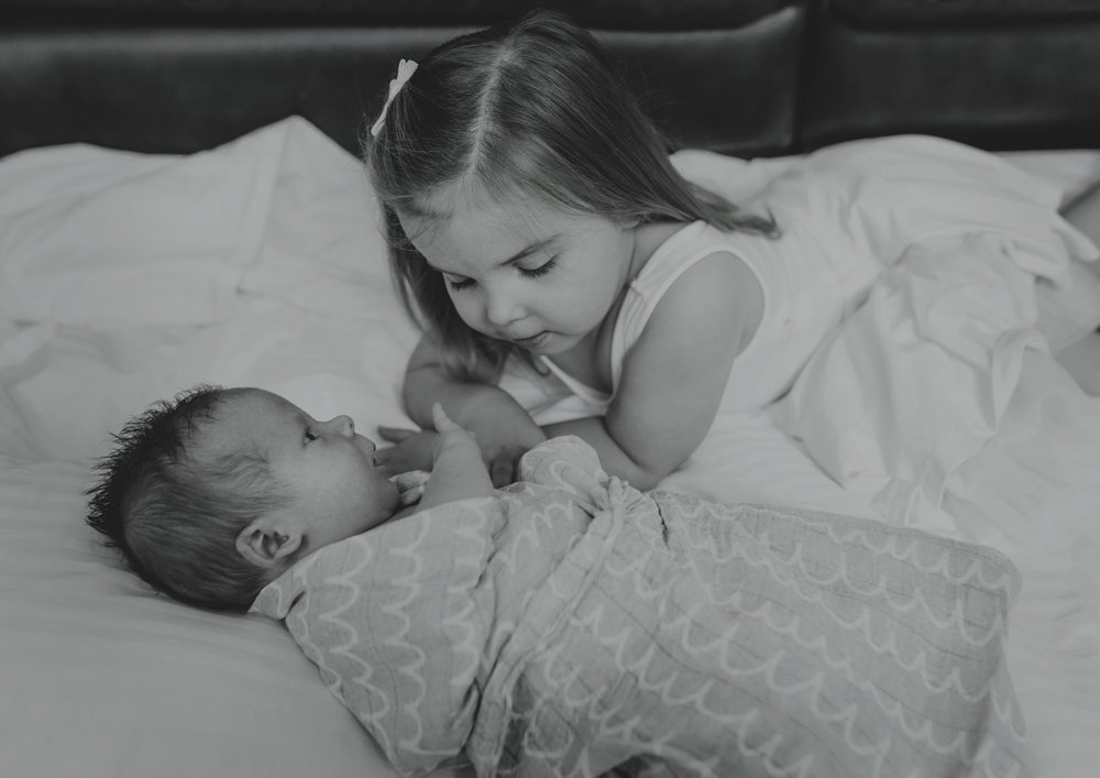Big sister loves her newborn baby brother