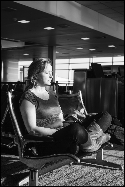 a woman sleeps at an airport.jpg
