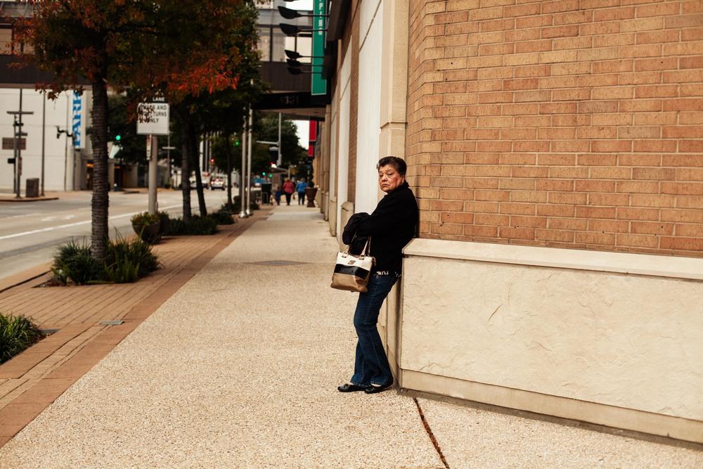 a woman waits on a street corner.jpg