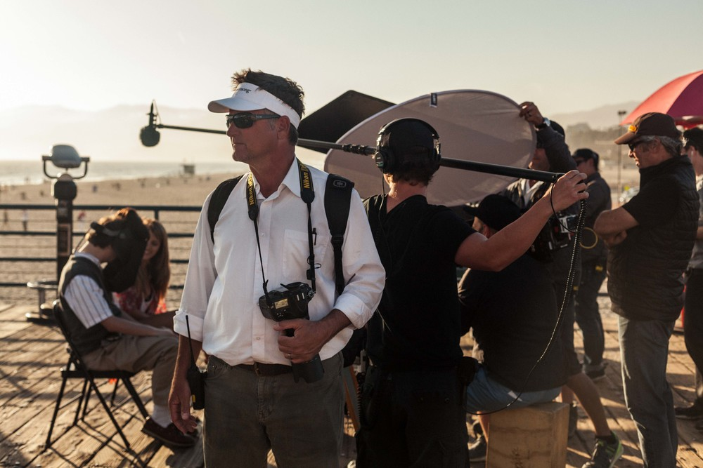 a set photographer stands by while they film.jpg