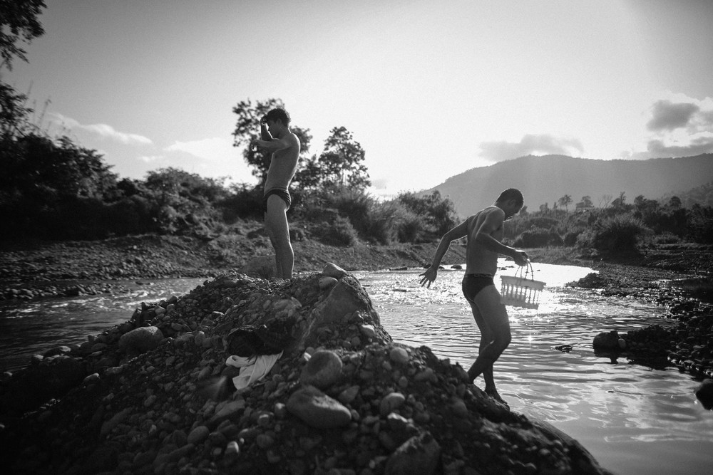 Two recovering addicts at the Aung Mintha rehab play in a stream near the rehab camp. The cold water eases their withdrawal pains.